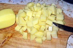 Картофель нарезанный кубиками на разделочной доске (фото)
